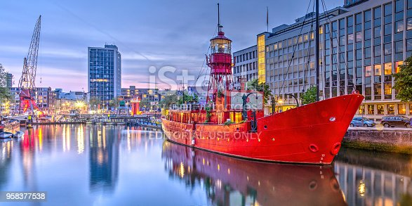 Rotterdam, The Netherlands, May 3, 2017: Panoramic view of Wijnhaven harbour at dusk with a former red light vessel, now a restaurant