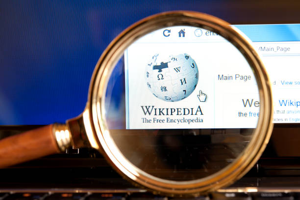 Wikipedia website through a magnifying glass stock photo