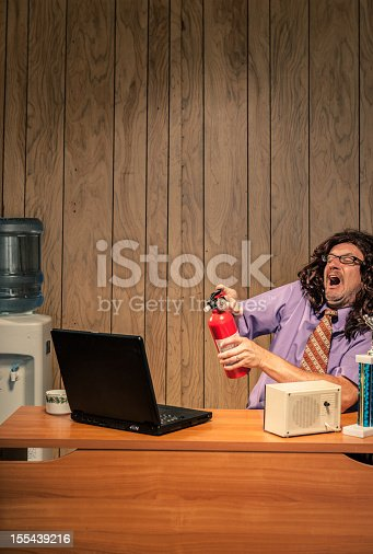 618210072 istock photo Wild and crazy IT man spraying computer with fire extinguisher 155439216