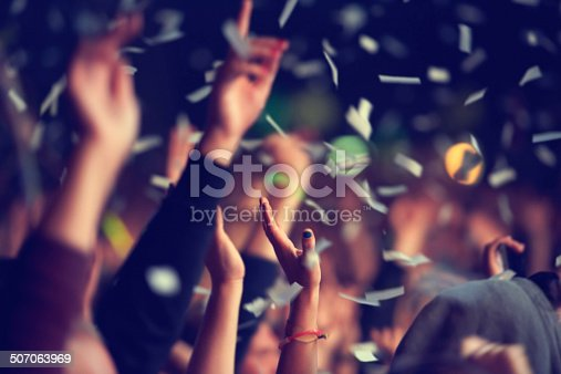 A music festival audience throwing confetti into the air in celebration