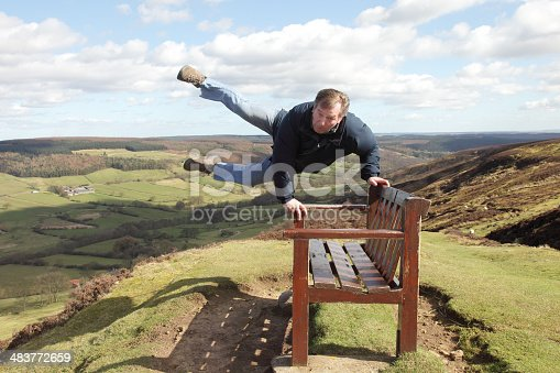 A man clings onto a bench in strong winds at the top of Rosedale Chimney Bank on the North York Moors, Yorkshire, England.