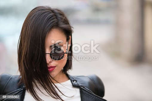 Headshot of a beautiful young woman with sunglasses.