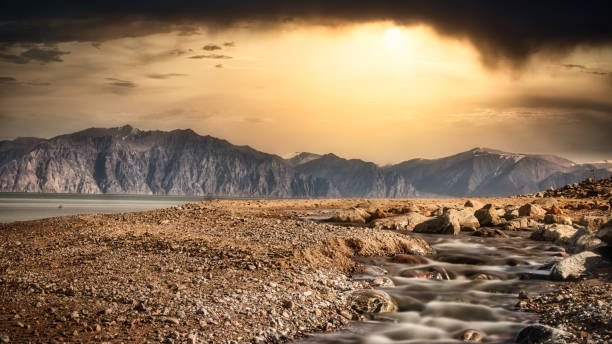 Wild beach over mountains and dramatic sky. stock photo
