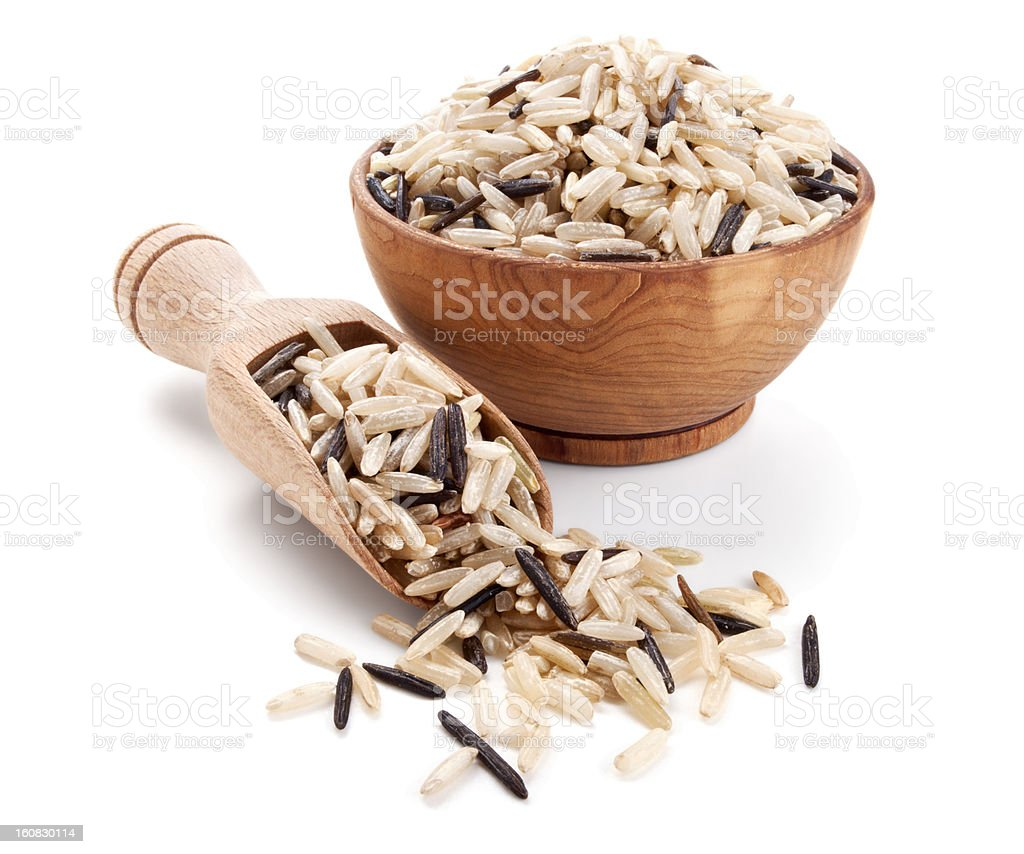 wild brown rice in a wooden bowl isolated on white stock photo