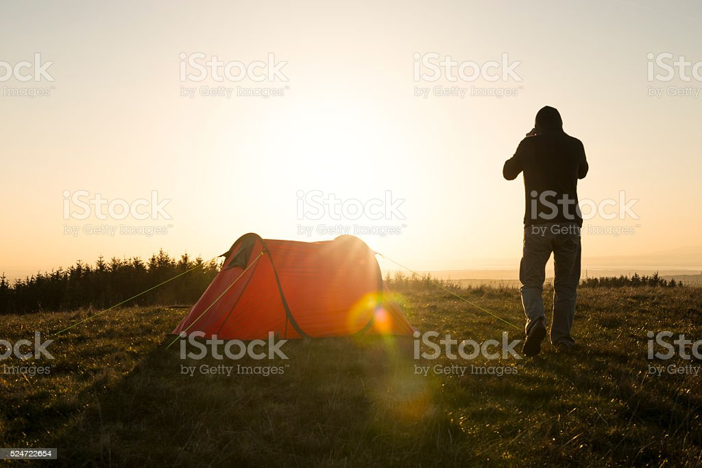Wild Camping, Man with red tent in remote countryside. stock photo