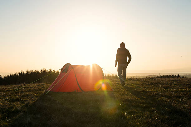 wild camping, man with red tent in remote countryside. - tent stock photos and pictures