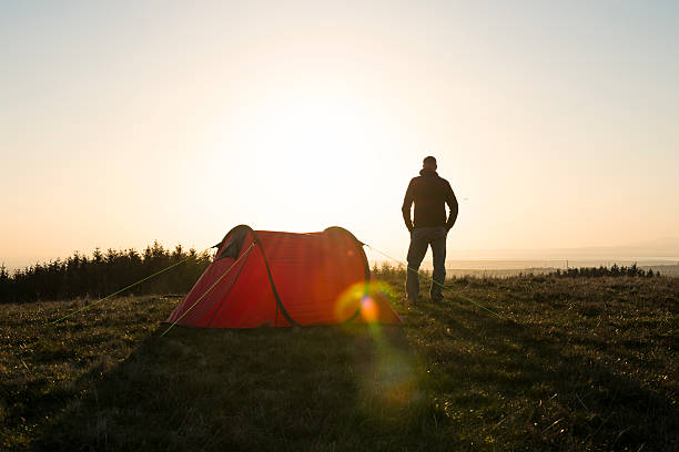 wild camping, man with red tent in remote countryside. - tent stock pictures, royalty-free photos & images