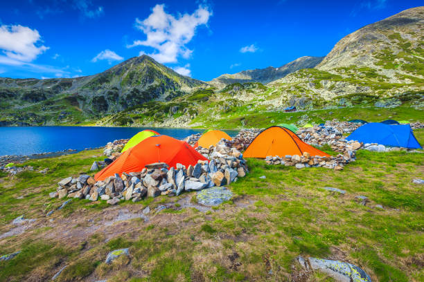 Wild camping place with colorful tents in the mountains, Romania stock photo
