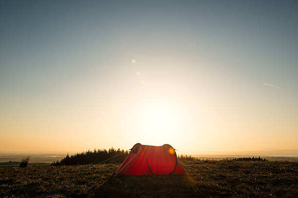 wild camping, red tent in remote countryside, sun flare. - tent stock pictures, royalty-free photos & images