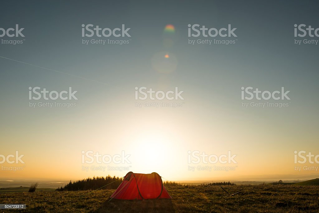 Wild Camping, red tent in remote countryside, sun flare. stock photo