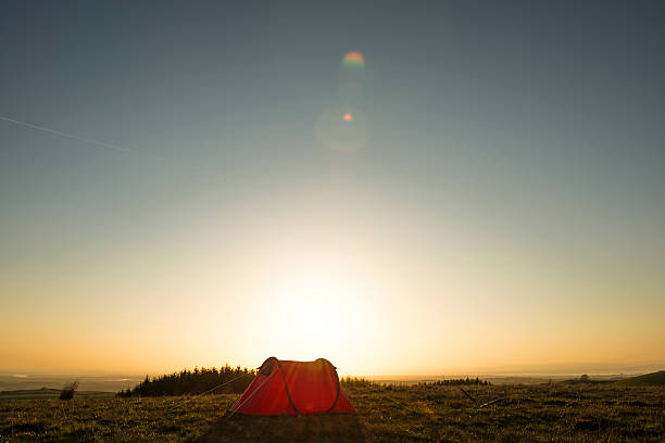 wild camping, red tent in remote countryside, sun flare. - tent stock photos and pictures