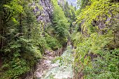 Scenic view of canyon Kaiserklam in Tirol, Austria with a wild stream of blue to green colored water.