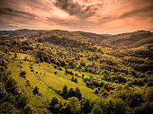 Drone shot depicting a high angle view of a beautiful forested landscape in the foothills of the Carpathian mountains of Romania. The lush wilderness is set off by a glowing sunset and cloudscape.
