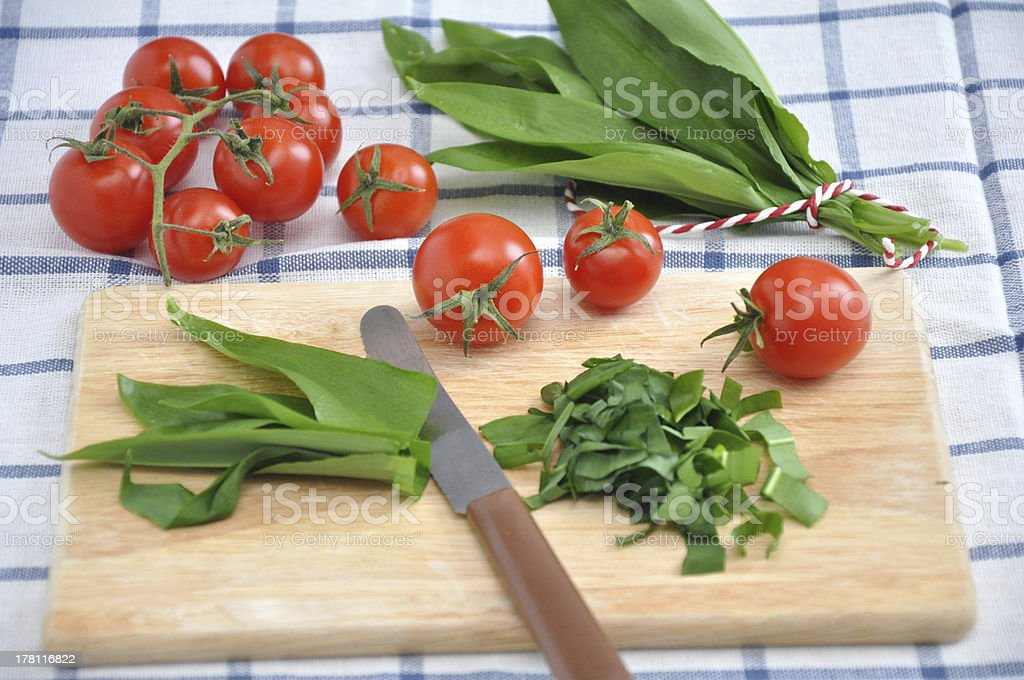Wild garlic with tomatoes on a wooden board stock photo