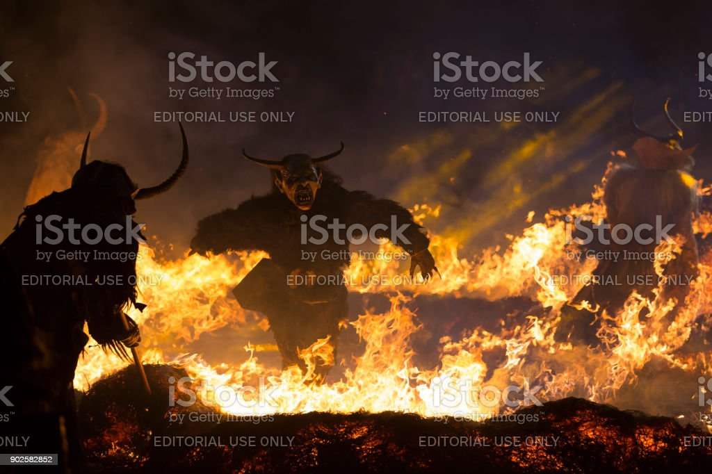 Wild Krampus characters running around fire stock photo