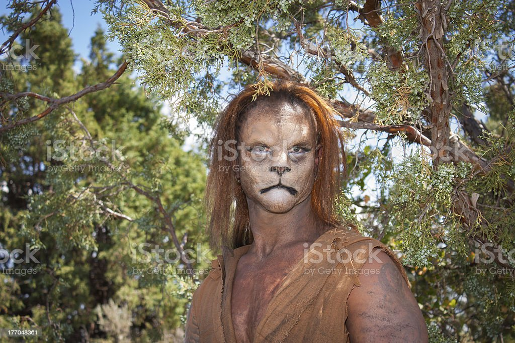 Wild Lion Man in forest A Wild Lion man stares cautiously at the camera with a background of forest.  This is the fantastic make-up done by Rayce Bird. Acting - Performance Stock Photo