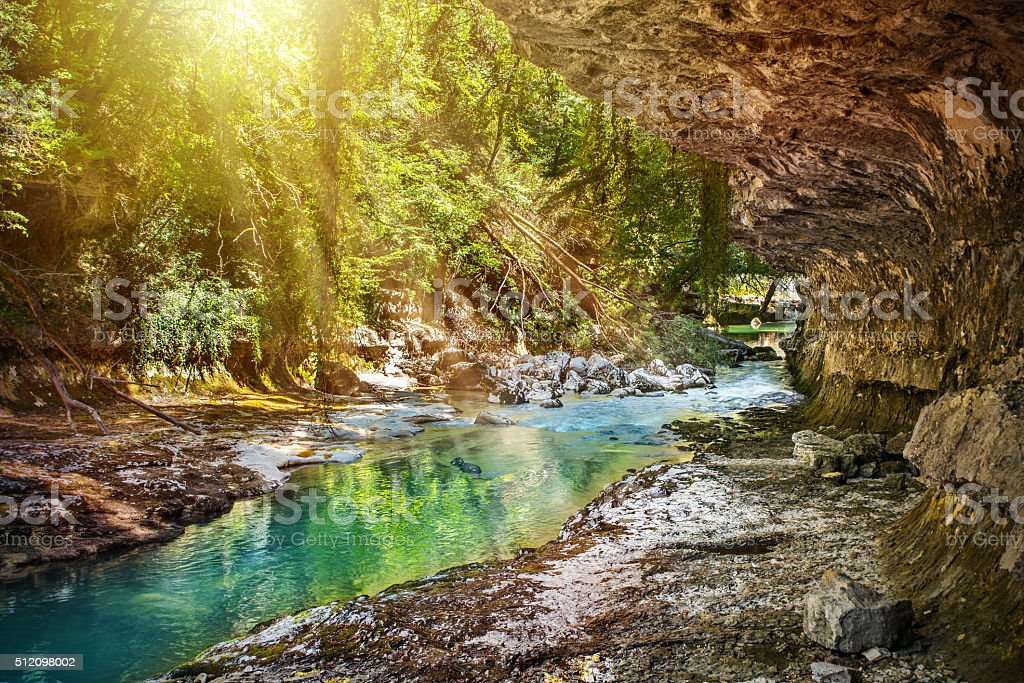 Wild rapid riverbed eroded with rock formation in lush forest stock photo