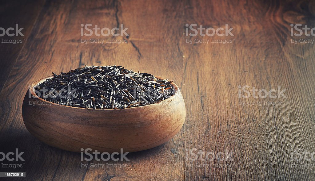 wild rice in a wooden bowl stock photo