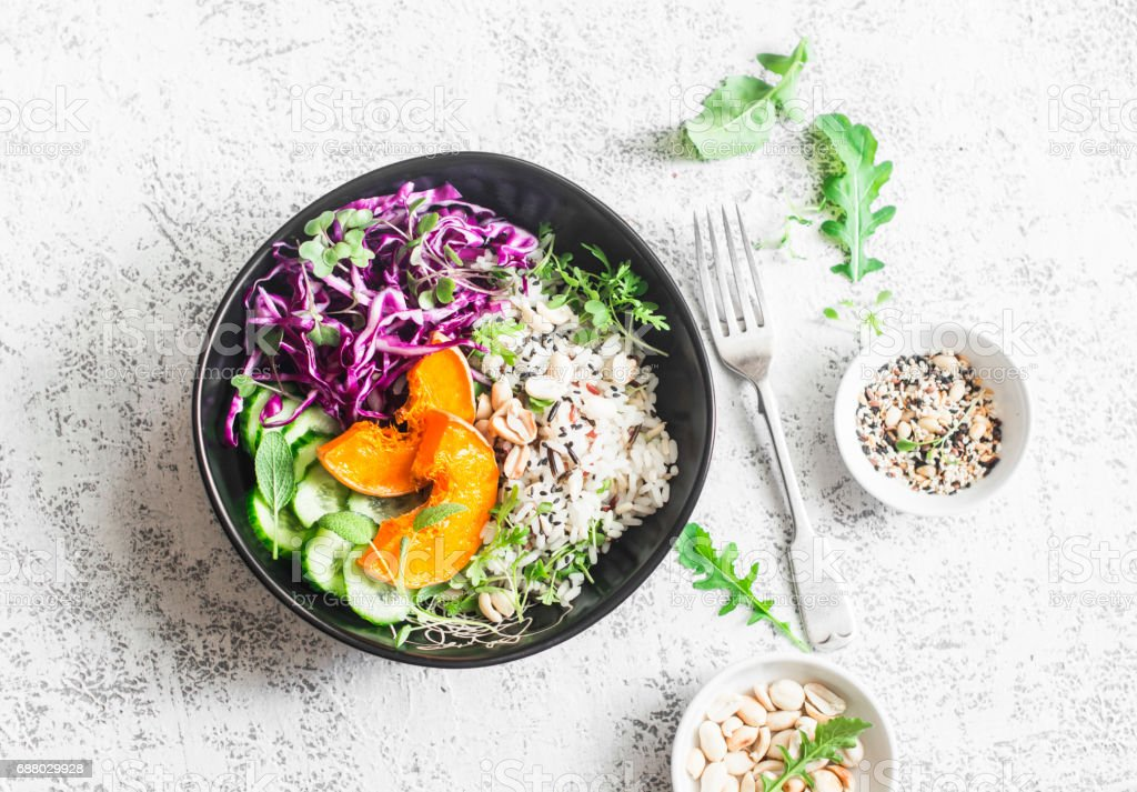Wild rice, roasted pumpkin, red cabbage buddha bowl. Vegetarian food concept. On a light background, top view stock photo