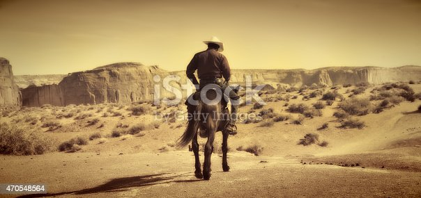 Native American Indian cowboy riding away on saddle horse in the Monument Valley Tribal Park desert landscape, Utah and Arizona border, USA. The American Southwest plateau in a panoramic format, with desaturated sepia tone effect, provides an old, antique, retro revival Wild West impression. Horizontal scenic view with copy space.