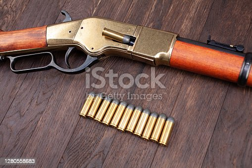 Wild west gun - lever-action repeating rifle with ammunition on wooden table