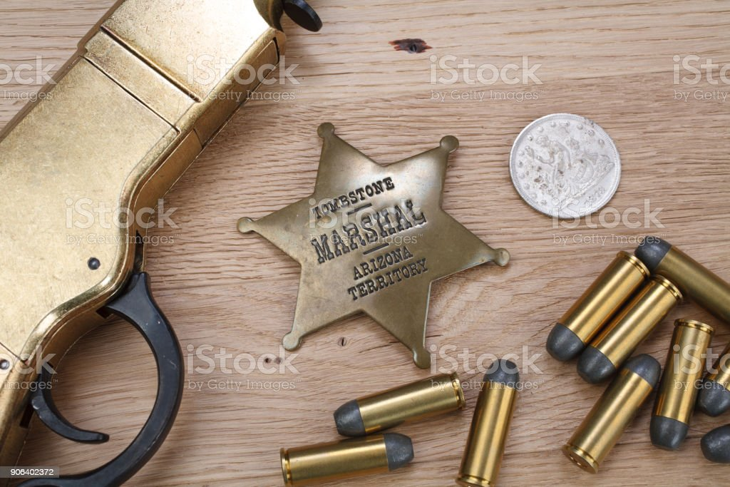 Wild west period repeating rifle with ammunition and sheriff badge stock photo