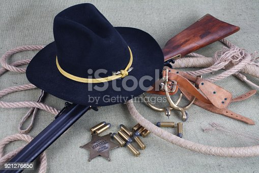 istock Wild west period repeating rifle with ammunition and sheriff badge 921276650