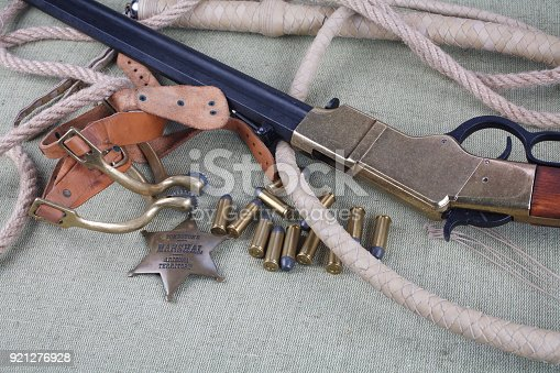 istock Wild west period repeating rifle with ammunition and sheriff badge 921276928