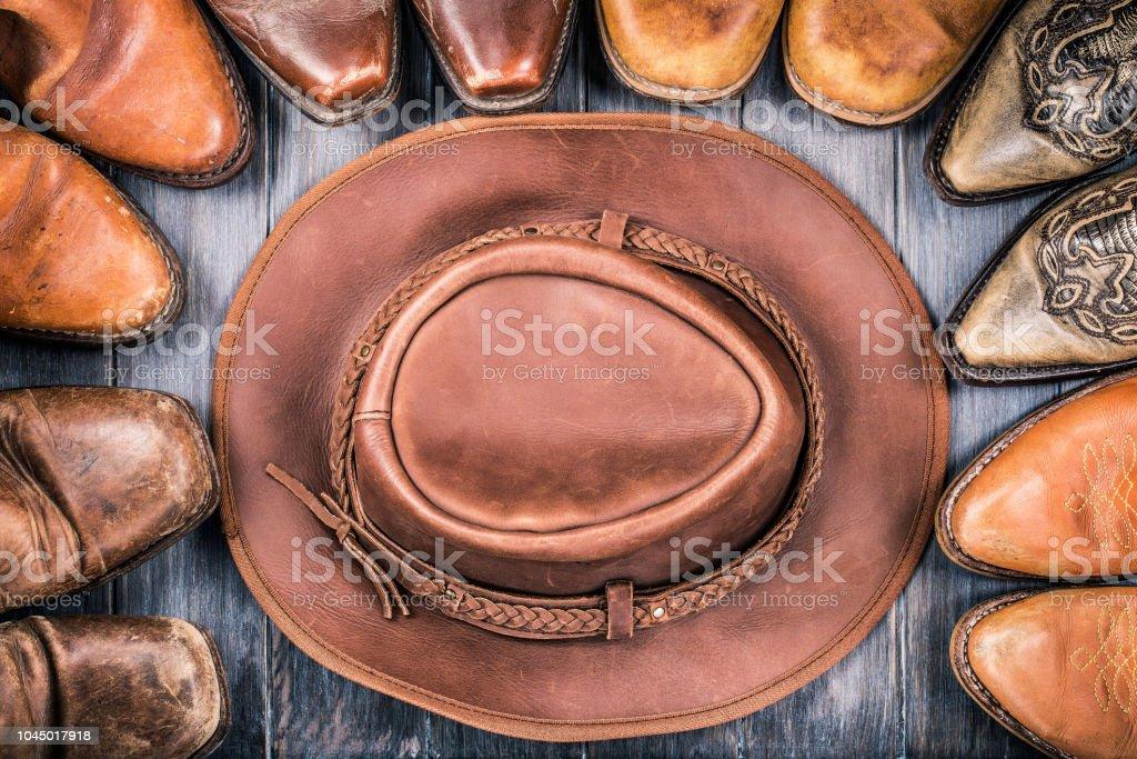 Chapéu de cowboy retrô do oeste selvagem e couro velho botas no chão de  madeira. 5efecca68c3