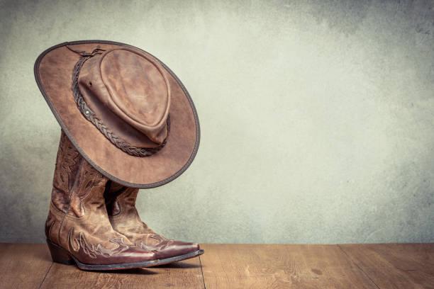 viejo frente de botas y sombrero de vaquero de cuero retro salvaje oeste fondo de pared de hormigón. foto filtrada de estilo vintage de instagram - bota fotografías e imágenes de stock
