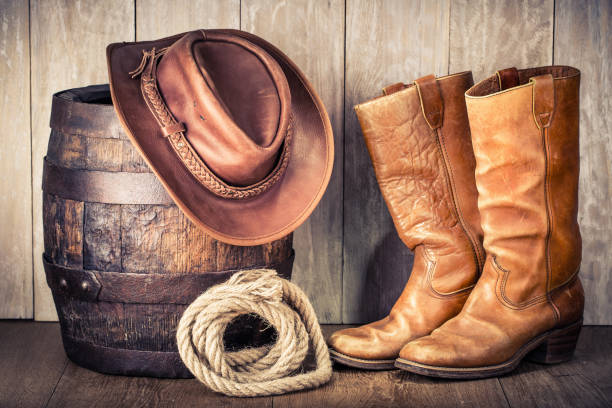 Wild West retro leather cowboy hat, old boots and oak barrel. Vintage style filtered photo Wild West retro leather cowboy hat, old boots and oak barrel. Vintage style filtered photo bandit stock pictures, royalty-free photos & images