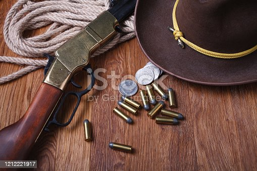 Wild west rifle, ammunition and silver dollars on wooden table