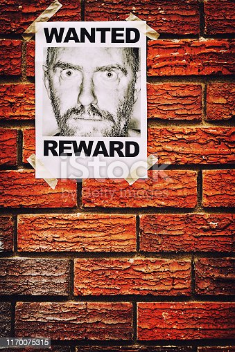 Wanted poster stuck on wall.