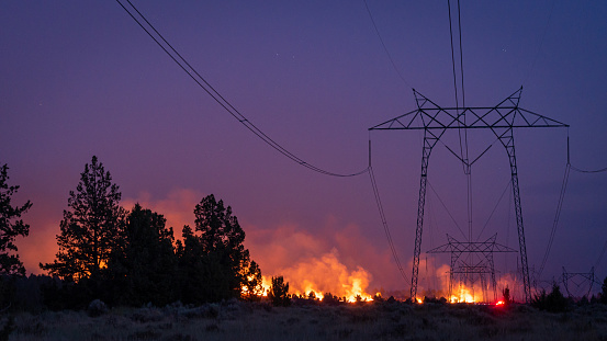 a california wildfire burns under a high voltage electrical transmission line