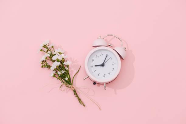 wildblumen bouquet und retro-wecker mit schatten auf rosa hintergrund - blumenuhr stock-fotos und bilder