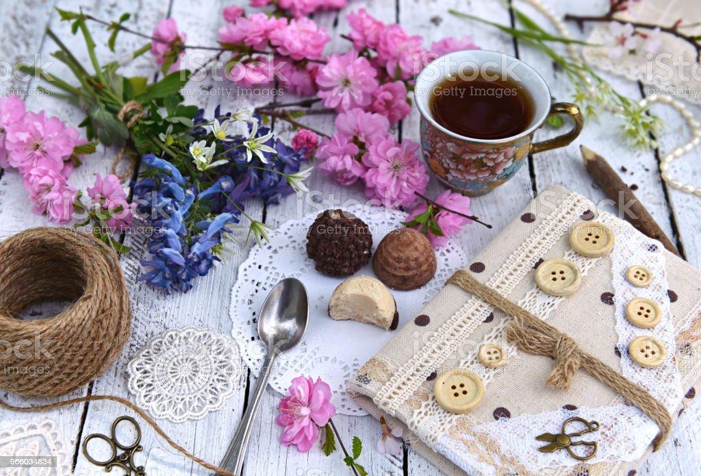 Wildblumen, Zweige Kirschbaum in voller Blüte, Tasse Tee und Tagebuch auf Brettern - Lizenzfrei Altertümlich Stock-Foto