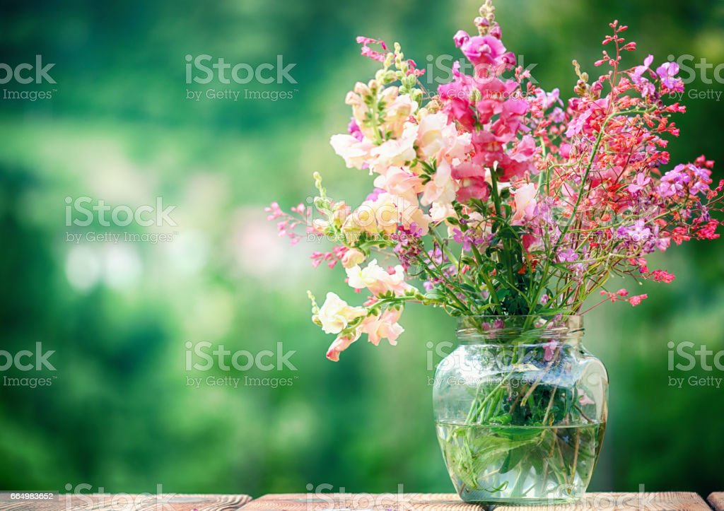 Wildflowers in a Glass Vase over Green Background – zdjęcie