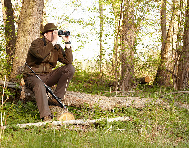 Wildlife hunting requires patience A game ranger looking through his binoculars while sitting on a log park ranger stock pictures, royalty-free photos & images