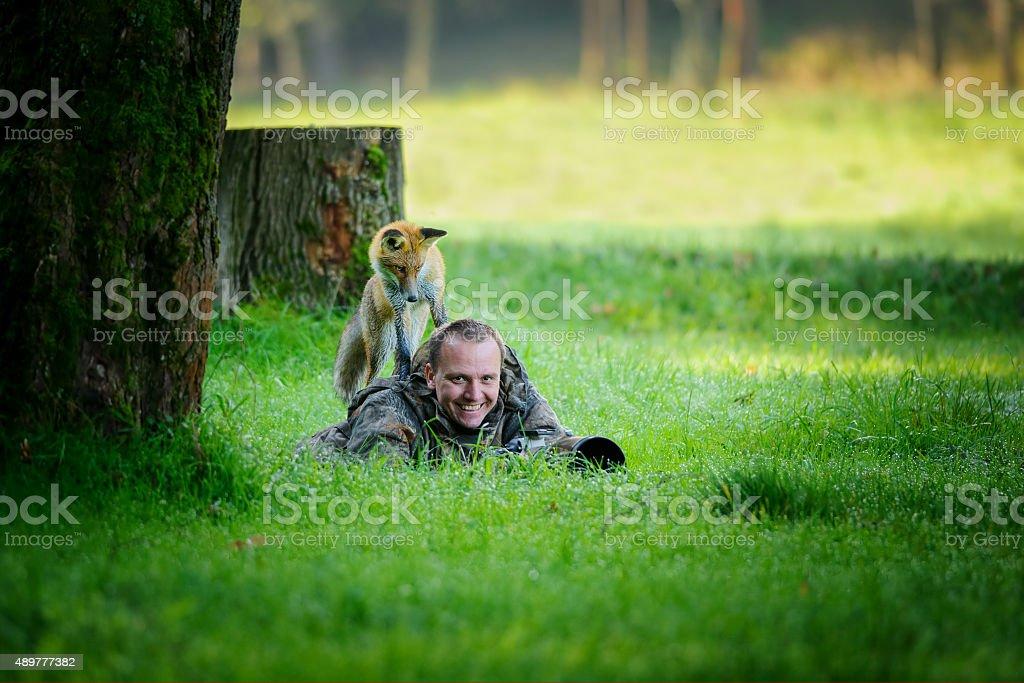 Fotografen im Gras mit seltsamen fox auf dem Rücken – Foto