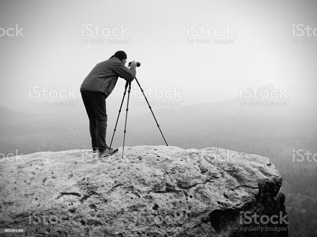 Wildlife photographer on mountain summit works. Man like to travel and photography, taking pictures stock photo