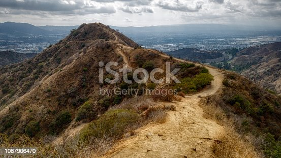 Stunning view of Wildwood Canyon Trail winding along a steep ridge on a cloudy day, with scenic overlook of Burbank, California