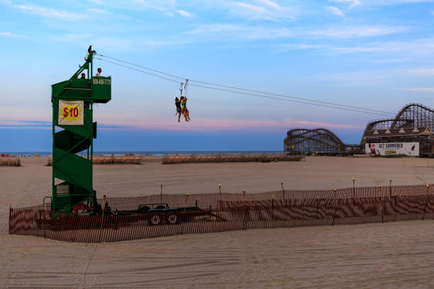 Wildwood NJ boardwalk on a summer evening with the piers and activity stock photo