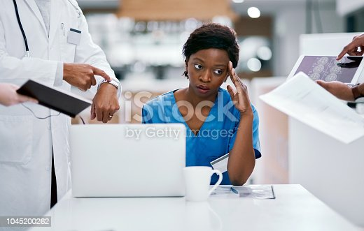 Shot of a young doctor looking stressed out in a demanding work environment
