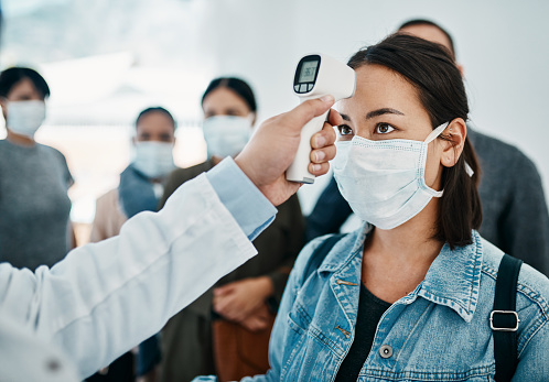 Shot of a young woman getting her temperature taken with an infrared thermometer by a doctor during an outbreak