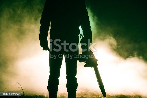 Man holding chainsaw at night