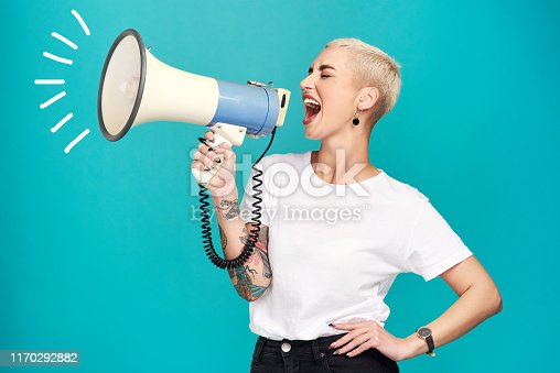 Studio shot of a young woman using a megaphone against a turquoise background