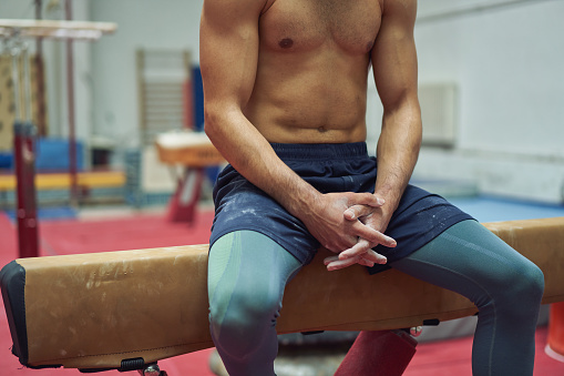 Portrait of a confident shirtless young male gymnast sitting on a pommel horse