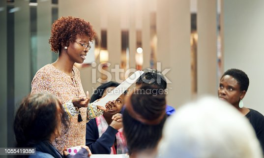 Shot of a confident young woman reading from a piece of paper to other women seated at a table during a meeting inside a community centre