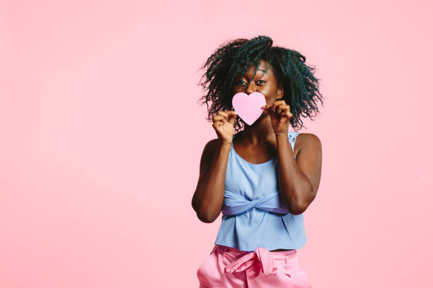 Will you be mine? Portrait of a shy young woman  and holding a pink heart  and peeking over it, isolated on pink studio background love at first sight stock pictures, royalty-free photos & images