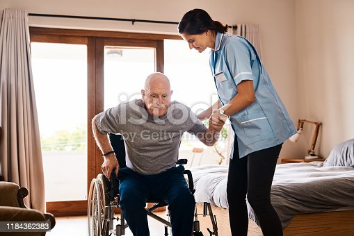 Shot of a young nurse helping a senior man get up from a wheelchair in a retirement home